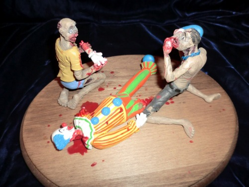 two zombies eating a clown